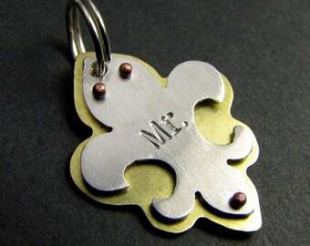brass and aluminum fleur de lis pet tag