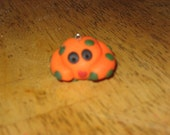 round orange polka dot monster polymer clay charm