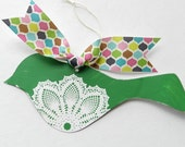 Green  tin bird with white doily and colorful ribbon