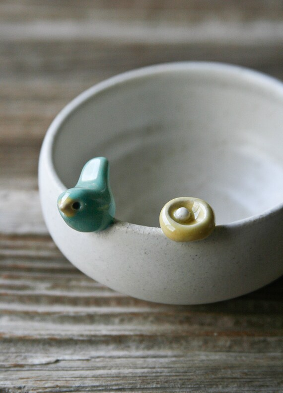 Sweet Little Light Green Bird on a White Bowl with Nest