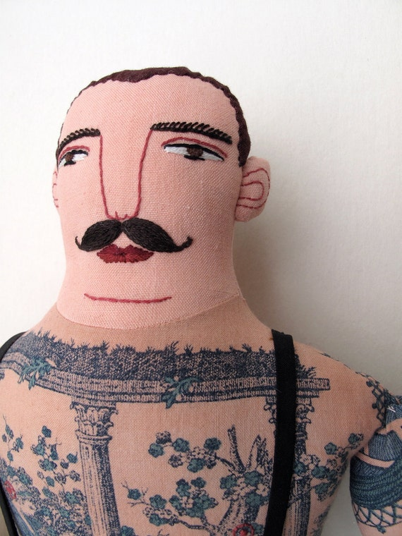 Tattooed man with mustache doll