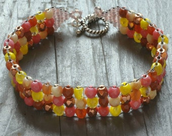 warm tones bracelet. square-stitched czech glass beads of salmon, yellow, cream & carnelian with sterling silver toggle clasp by val b.rl