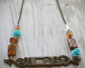 le fleur gatekeeper necklace. vintage brass escutcheon keyhole plate & czech glass by val b.
