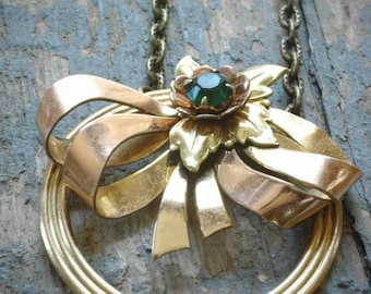 vintage re-purposed emerald rhinestone and gold-filled bow and wreath necklace on antiqued brass chain. ooak by val b.