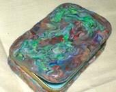 Multi-colored swirled design on a metal tin