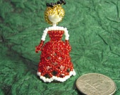 beaded miniature figurine in red dress