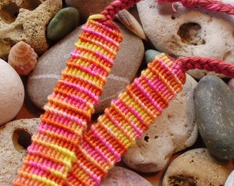 Variegated friendship bracelet in pink, orange, yellow and red