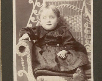 Impish child in ornate seat button boots wicker smiling cute photo girl button