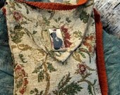 Hand sewn small tapestry cross body fabric bag in earth tones, with images of leaves and vines and image of woman in crackled resin