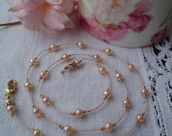 Peach pearl, Gold, and knotted silk necklace