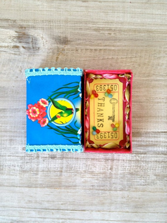 Altered vintage matchbox with a tropical bright greeting inside