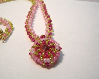Beadwoven necklace and pendant in pinks,green and rose colored crystals and seed beads