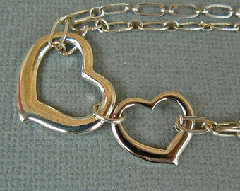 You And Me: Our hearts are connected, always.  Silver plated double heart bracelet.