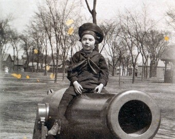 vintage photo  Cute little BOy in Sailor outfit sits on Cannon
