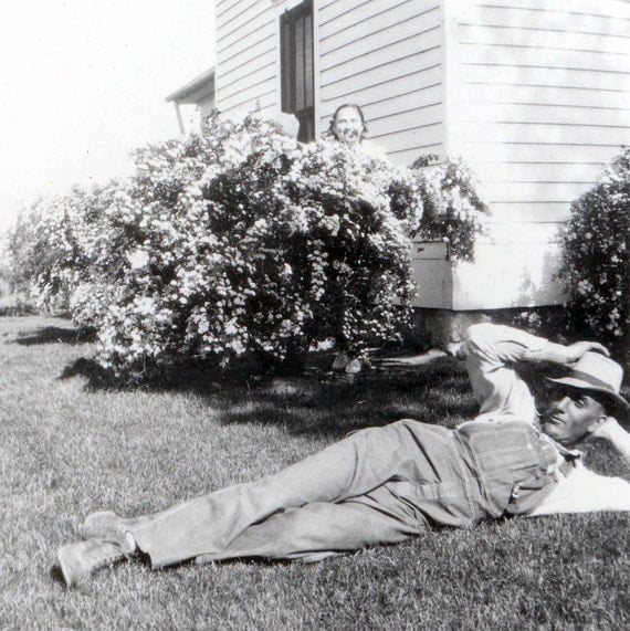 Vintage photo Man REsts on Lawn after Work Wife Hides in Bushes