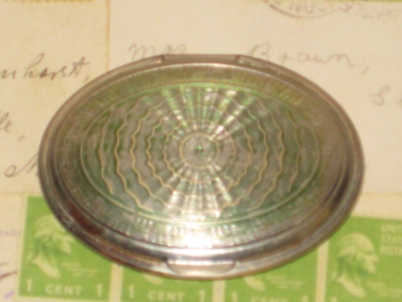 VINTAGE SMALL SILVERTONE OVAL COMPACT WITH INTACT MIRROR AND ENGRAVINGS INSIDE