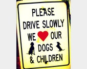 "Priorities: funny fine art photograph print of humorous sign saying, ""Please Drive Slowly, We Love Our Dogs and Children"" with red heart"