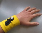Yellow wristband with navy blue lace applique and button
