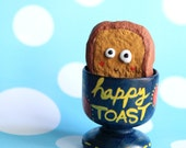 Happy Toast (clay) in a wooden egg cup
