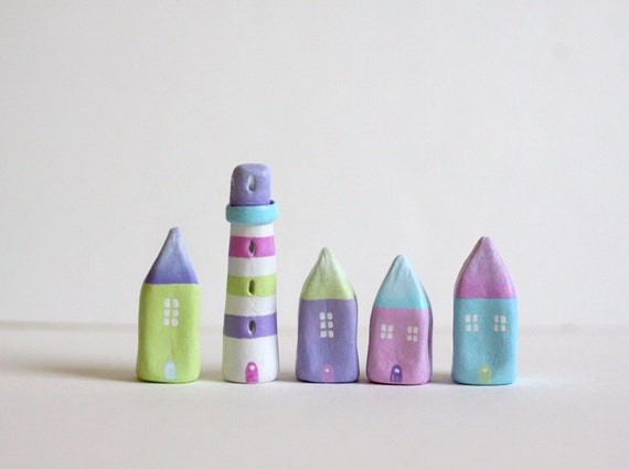 Little village with 4 pastel little clay houses and a striped lighthouse
