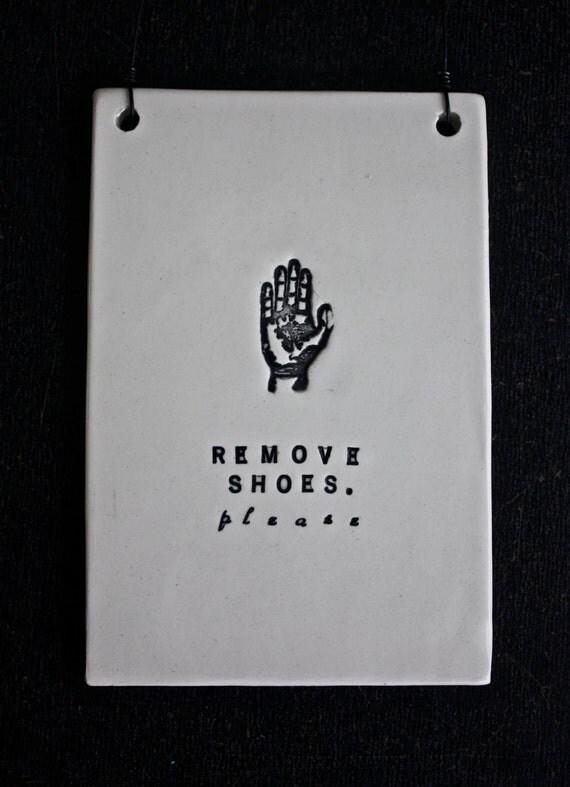REMOVE SHOES plaque (hand).