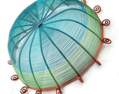 Sixteen sided copper wire basket in teal blue, green, and brown