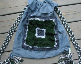 Upcycled and Reconstructed Jean Drawstring Bag With a Bright Crocheted pocket front.