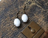 Antique brass earrings with a vintage opaque white stone