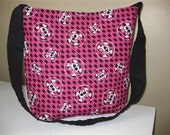 Pink and black houndstooth bag with skull and cross bones.