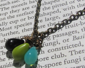 Watching me fall. A black, green, and teal glass drop necklace.