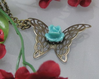 You give me butterflies (A teal blue rose and brass filigree butterfly necklace)