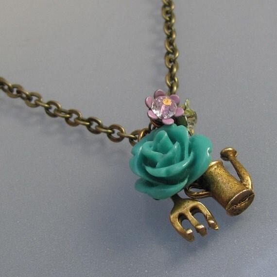 A gardeners, teal blue flower, watering can, vintage, pink enameled flower necklace.