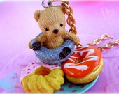 Sweet teddy bear loves donuts necklace with pink and orange frosted powdered donuts on turquoise polka dot plate