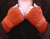 Knit fingerless gloves with a strap in burnt orange, mittens