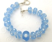 Bracelet of pale sky blue and white etched lampwork glass beads, crystal and sterling silver toggle clasp