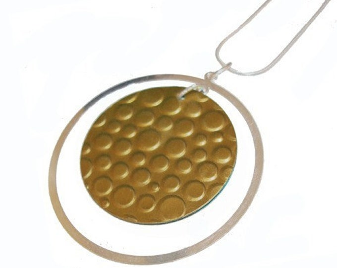 Recycled aluminum/sterling silver with circles and dots in brown/bubbles in fuchsia on the back