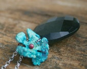 Moss Aquamarine briolette decorated with a verdigris brass flower on sterling silver necklace