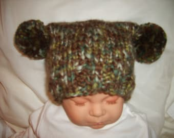 Camouflage colored baby hat with pom-poms. Sized for 0 to 6 mths. Bulky, thick and thin.