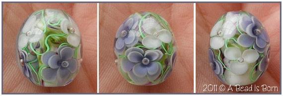 A Bead is Born handmade lampwork glass bead encased roses purple white green vines swirled background