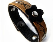 Distressed tan leather bracelet with black stitching and flower accent