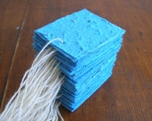 Cobalt blue tags made of handmade plantable paper embedded with perennial and annual flower seeds