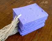 Purple tags made of handmade plantable paper embedded with perennial and annual flower seeds