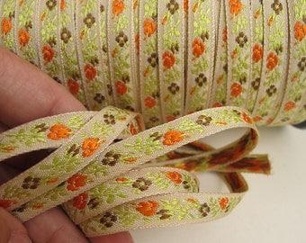 3 yards narrow Daisies and Roses Jacquard trim. Orange, brown, kiwi green on ecru. 3/8 inch wide. 901-A Bavarian dress trim