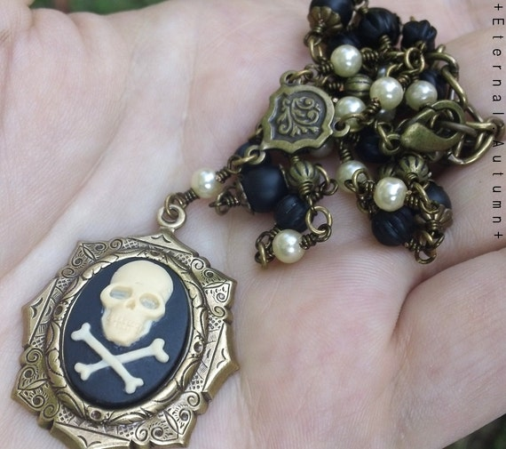 D r e a d. P i r a t e. R o b e r t s. Skull and Crossbones cameo pendant necklace in brass with faux pearls and Czech glass