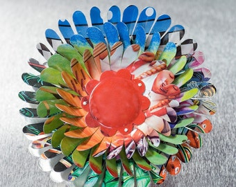 Multicolor Flower  Brooch with green, blue, orange and red Center surrounded by girl with braids  by Harriete Estel Berman