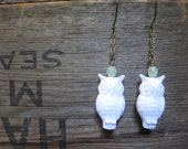 Vintage white lucite owls hang from antique brass chain earrings