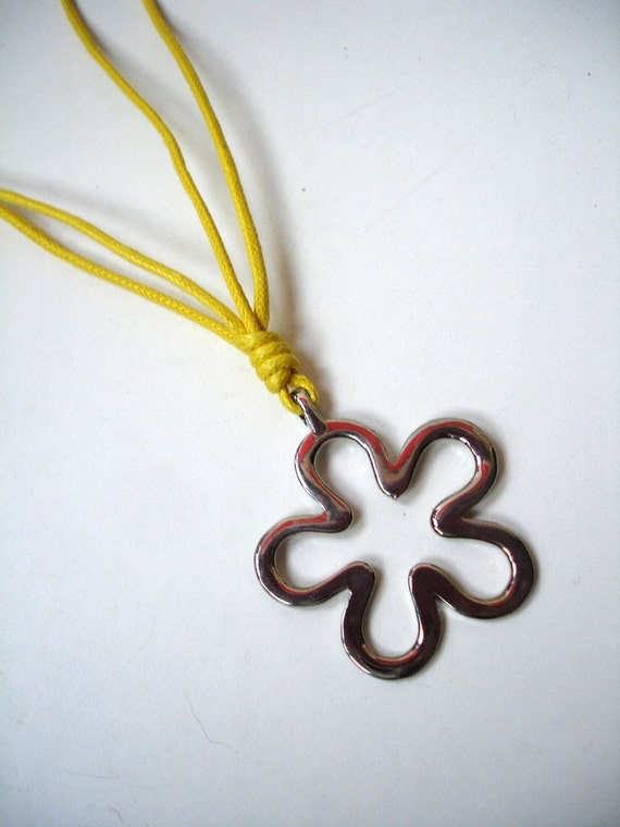 Silver flower pendant on a yellow cord