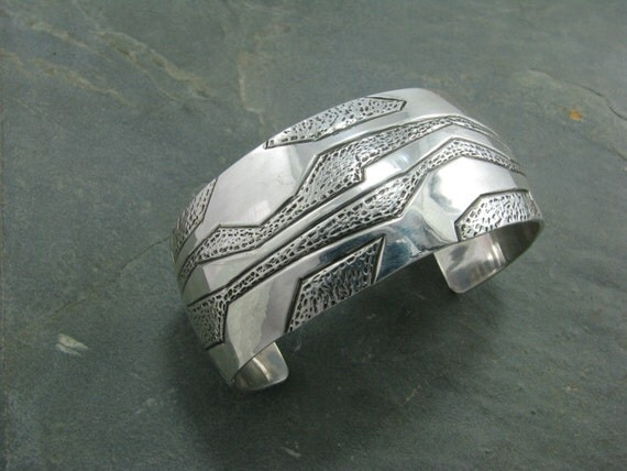 One inch wide domed abstract hand tooled bracelet