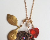 Vintage charm necklace with red Swarovski crystal heart, leaf spray charm & a 1940's recycled brooch  as focal point.