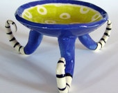 bright ceramic dish with stripe curly legs